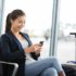 Airport business woman on smart phone at gate waiting in termina