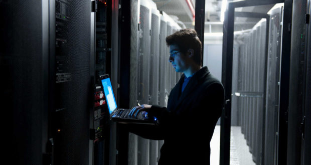 An IT technician programming computer equipment in a server room